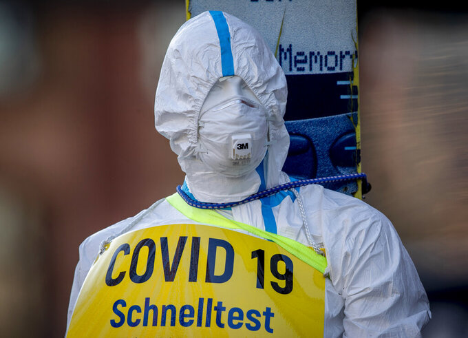 FILE - In this March 7, 2021 file photo an advertising figure for Covid-19 rapid test stands in front of a small test center in Frankfurt, Germany. (AP Photo/Michael Probst, file)