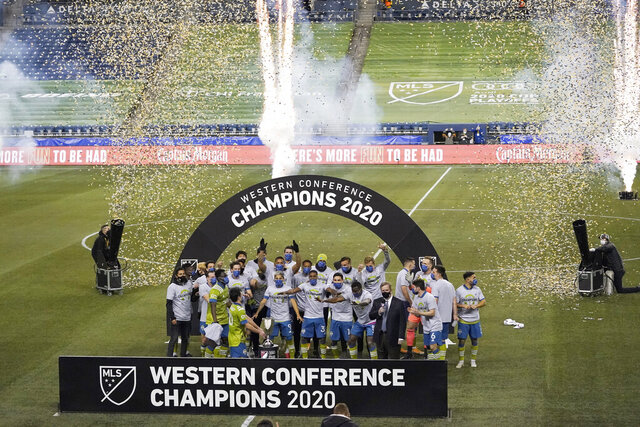 Seattle Sounders players celebrate with the championship trophy after the team beat Minnesota United in an MLS playoff Western Conference final soccer match, Monday, Dec. 7, 2020, in Seattle. The Sounders won 3-2. (AP Photo/Ted S. Warren)