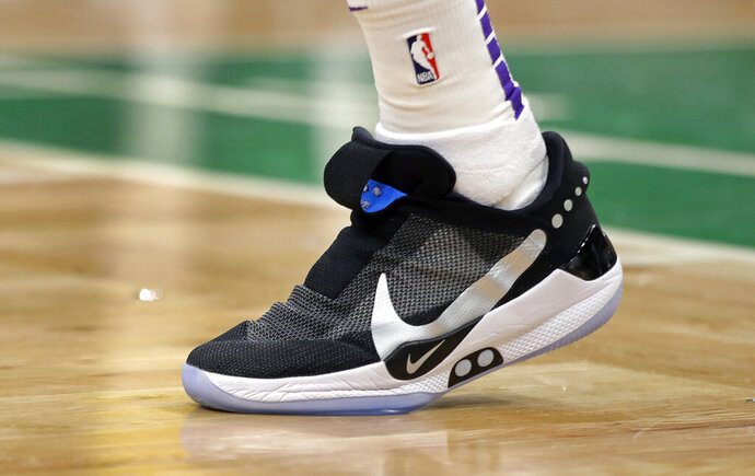 In this Feb. 7, 2019, photo, Los Angeles Lakers forward Kyle Kuzma walks on the court during an NBA basketball game against the Boston Celtics in Boston. He is wearing Nike's latest performance basketball shoes, which from concept to reality, took about three years to put together. Or 30 years, depending on how you count. The Nike Adapt BB _ a self-lacing smart shoe that can be controlled by a smartphone _ gets released to the public on Sunday, Feb. 17, 2019, a date that just happens to coincide with the NBA All-Star Game in Charlotte. It has a motor embedded within the shoe, and a hefty $350 price tag. It has a motor embedded within the shoe, and a hefty $350 price tag. (AP Photo/Elise Amendola)