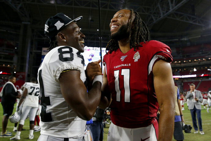 Oakland Raiders wide receiver Antonio Brown (84) and Arizona Cardinals wide receiver Larry Fitzgerald (11) meet at midfield after an an NFL preseason football game, Thursday, Aug. 15, 2019, in Glendale, Ariz. The Raiders won 33-26. (AP Photo/Rick Scuteri)