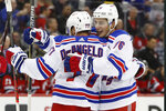 New York Rangers' Brady Skjei, right, embraces defenseman Tony DeAngelo (77), who scored a goal during the first period of an NHL hockey game against the New Jersey Devils on Thursday, Oct. 17, 2019, in Newark, N.J. (AP Photo/Kathy Willens)