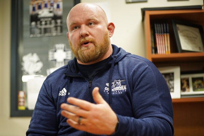 "In this March 2, 2020, photo, Concordia University wrestling coach Levi Calhoun speaks in his office in Seward, Neb. Calhoun knew that Tanner Farmer, the former Nebraska football player, would definitely be a force in the NAIA, but did not expect him to be as dominant as he has been."" (AP Photo/Nati Harnik)"