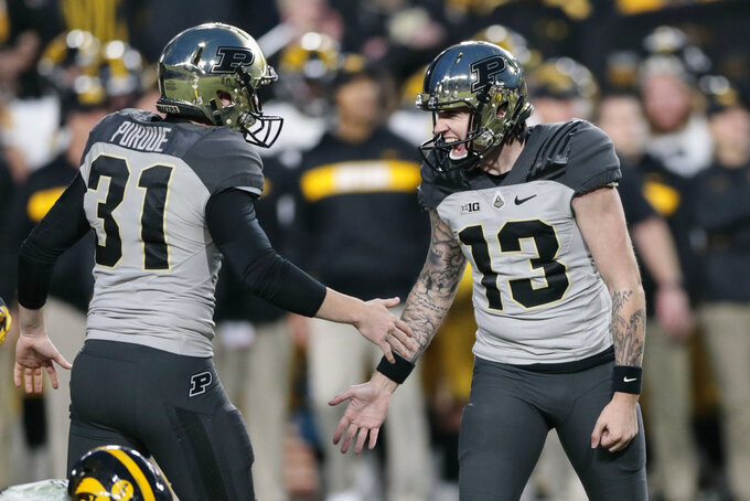 Purdue placekicker Spencer Evans (13) is congratulated by punter Joe Schopper (31) after booting the winning field goal in the fourth quarter of an NCAA college football game against Iowa in West Lafayette, Ind., Saturday, Nov. 3, 2018. (AP Photo/AJ Mast)