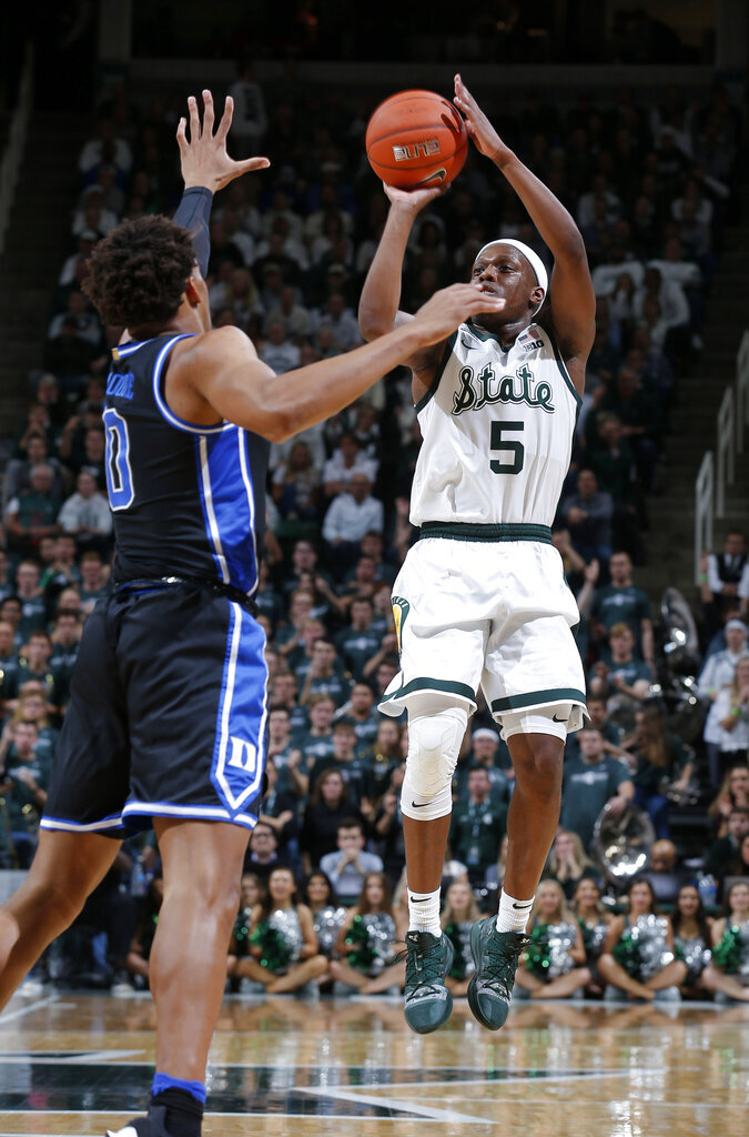 Michigan State's Cassius Winston, right, shoots as Duke's Wendell Moore defends during the second half of an NCAA college basketball gamet Tuesday, Dec. 3, 2019, in East Lansing, Mich. Duke won 87-75. (AP Photo/Al Goldis)