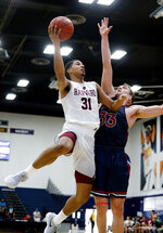 File-This Nov. 23, 2017, file photo shows Harvard forward Seth Towns, left, going to the basket while defended by Saint Mary's forward Kyle Clark during the second half of an NCAA college basketball game in Fullerton, Calif.  Although the Ivy League won't have a basketball season this year, a few of its most notable recent performers will be playing for new schools in different conferences. Former Harvard stars Bryce Aiken and Towns, as well as ex-Yale standout Jordan Bruner, left as graduate transfers during the offseason. Aiken headed to Seton Hall, Towns joined No. 23 Ohio State and Bruner opted to finish his career in Alabama. (AP Photo/Ringo H.W. Chiu, File)