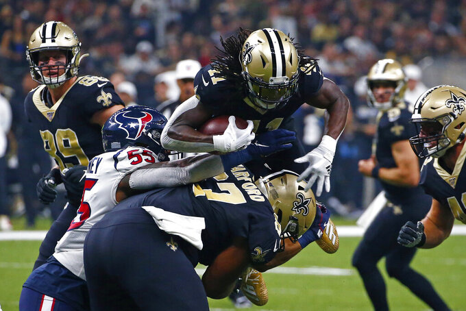 New Orleans Saints running back Alvin Kamara dives over Houston Texans inside linebacker Benardrick McKinney (55) as offensive guard Larry Warford (67) blocks in the first half of an NFL football game in New Orleans, Monday, Sept. 9, 2019. (AP Photo/Butch Dill)