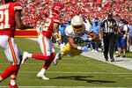 Los Angeles Chargers' Austin Ekeler (30) dives in for a touchdown past Kansas City Chiefs' Tyrann Mathieu (32) and Mike Hughes (21) during the first half of an NFL football game, Sunday, Sept. 26, 2021, in Kansas City, Mo. (AP Photo/Charlie Riedel)