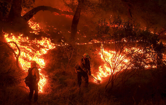 Cal Fire personnel set a backfire during the Hennessey fire in Napa County, Monday, August 17, 2020. (Kent Porter//The Press Democrat via AP)