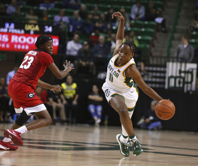 Baylor guard Jordyn Oliver, right, hangs on to the ball while driving past Georgia guard Que Morrison, left, in the second half of an NCAA college basketball game, Wednesday, Dec. 4, 2019, in Waco, Texas. (Rod Aydelotte/Waco Tribune-Herald via AP)