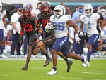 North Carolina running back Javonte Williams (25) runs the ball as Miami cornerback Te'Cory Couch (23) and Bubba Bolden (21) give chase during the first half of an during an NCAA college football game at Hard Rock Stadium In Miami Gardens, Fla, Saturday, Dec, 12, 2020. (Al Diaz/Miami Herald via AP)