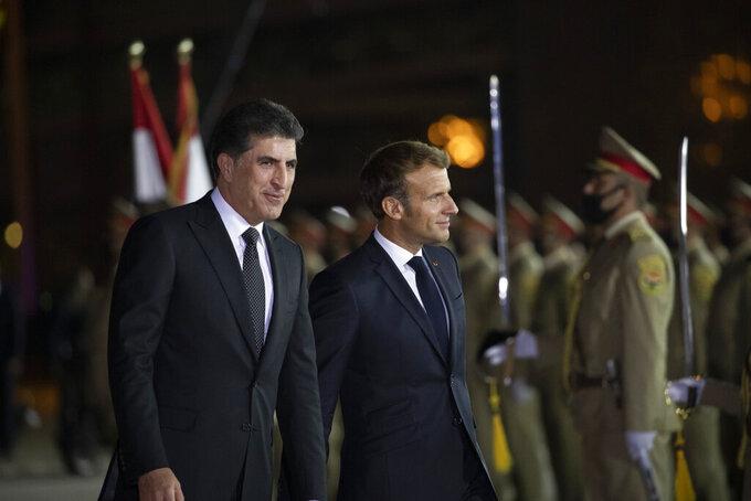 Kurdish President Nechirvan Barzani, left, welcomes French President Emmanuel Macron upon his arrival to Irbil airport, Iraq, early Sunday, Aug. 29, 2021. (AP Photo/Hadi Mizban)