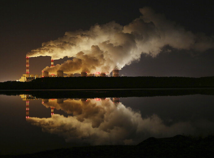 FILE - In this Wednesday, Nov. 28, 2018 file photo, clouds of smoke over Europe's largest lignite power plant in Belchatow, central Poland. Greenhouse gas emissions in the European Union have been reduced by 24% compared to 1990 levels, according to the bloc's annual climate report. Still, the EU said Monday, Nov. 30, 2020 it need to intensify efforts to make its target of making Europe the first climate neutral continent by mid-century. (AP Photo/Czarek Sokolowski, file)