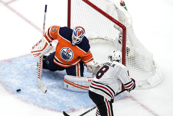 Edmonton Oilers goalie Mikko Koskinen (19) makes a save against Chicago Blackhawks' Dominik Kubalik (8) during third-period NHL hockey Stanley Cup playoff game action in Edmonton, Alberta, Saturday, Aug. 1, 2020. (Jason Franson/The Canadian Press via AP)