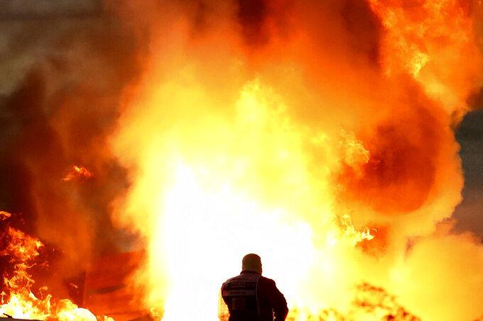 Staff extinguish flames from Haas driver Romain Grosjean of France's car after a crash during the Formula One race in Bahrain International Circuit in Sakhir, Bahrain, Sunday, Nov. 29, 2020. (Brynn Lennon, Pool via AP)