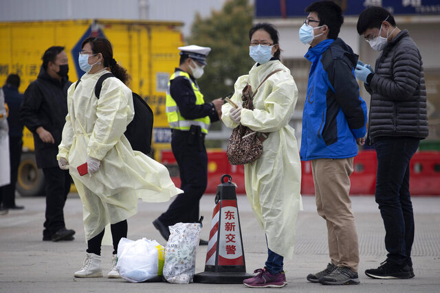 Residents wearing protective gear wait near a toll booth where some are entering the city of Wuhan which is still under lockdown due to the coronavirus outbreak but have started allowing some residents to return in central China's Hubei province on Thursday, April 2, 2020. (AP Photo/Ng Han Guan)