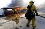 FILE - In this Oct. 10, 2019, file photo, firefighters try to protect surrounding homes as they battle the Sandalwood Fire in the Villa Calimesa Mobile Home Park in Calimesa, Calif. A deadly blaze that tore through the Southern California mobile home community this month started when a trash truck caught fire and the driver dumped the burning garbage on the side the road. Now, the waste industry is reviewing longstanding guidance to drivers to dump burning trash to ensure their safety, limit truck damage and prevent explosions. (Jennifer Cappuccio Maher/The Orange County Register/SCNG via AP, File)