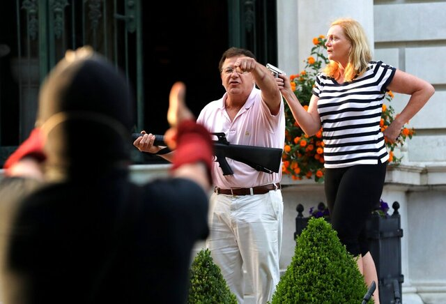 FILE - In this June 28, 2020 file photo, armed homeowners Mark and Patricia McCloskey, standing in front their house along Portland Place confront protesters marching to St. Louis Mayor Lyda Krewson's house in the Central West End of St. Louis. St. Louis' top prosecutor told The Associated Press on Monday, July 20, 2020 that she is charging a white husband and wife with felony unlawful use of a weapon for displaying guns during a racial injustice protest outside their mansion. (Laurie Skrivan/St. Louis Post-Dispatch via AP File)