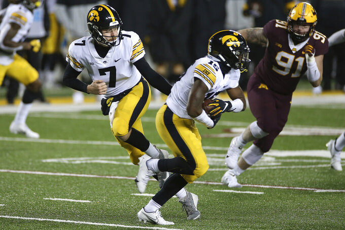 Iowa quarterback Spencer Petras (7) hands the ball off to running back Tyler Goodson (15) during the second half of the team's NCAA college football game against Minnesota, Friday, Nov. 13, 2020, in Minneapolis. Iowa won 35-7. (AP Photo/Stacy Bengs)