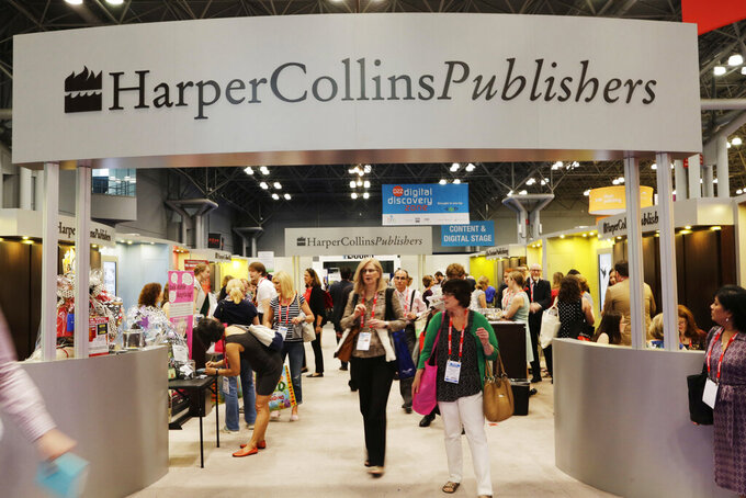 FILE - In this May 28, 2015 file photo, attendees at BookExpo America visit the HarperCollins Publishers booth in New York. The annual publishing convention and trade show, a decades-old tradition, may be coming to an end. ReedPop, which has managed BookExpo for a quarter century, announced Tuesday that it was dropping the event, along with the fan-based BookCon. (AP Photo/Mark Lennihan, File)