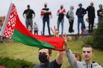 CORRECTING COUNTRY IN CAPTION TO BELARUS - People with Belarusian National flag gather in a street protesting the election results in Minsk, Belarus, Wednesday, Aug. 12, 2020. The demonstrators are contesting the official count showing President Alexander Lukashenko winning a sixth term with 80% of Sunday's vote, with crowds taking to the streets every night since to demand a recount. (AP Photo)