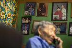 In this Monday, Jan. 20, 2020 image, family pictures hang on the wall as Lizzie Chimiugak talks on the phone at her home in Toksook Bay, Alaska. Chimiugak, who turned 90 years old on Monday, is scheduled to be the first person counted in the 2020 U.S. Census on Tuesday. (AP Photo/Gregory Bull)