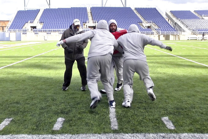 In this image provided by WaV Sports & Entertainment + The NFL Alumni Academy, Mike Tice, left, coaches at the NFL Alumni Academy at Tom Benson Stadium in Canton, Ohio on Nov. 4, 2020. In normal times, NFL teams sometimes must scramble to find players during the season when a wave of injuries or other issues hit. In 2020, multiply those needs exponentially because of the coronavirus pandemic. Helping out the 32 teams on a limited scale, for now, is the NFL Alumni Academy. (Devon Dalton/WaV Sports & Entertainment + The NFL Alumni Academy via AP)
