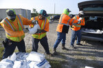 Corpus Christi city workers load free sandbags for residents ahead of Tropical Storm Beta, Saturday, Sept. 19, 2020, in Corpus Christi, Texas. The storm is expected to make landfall in South Texas early next week, with expected power outages and flooding in the region. (Annie Rice/Corpus Christi Caller-Times via AP)