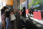 Protesters put adhesive notes on the doors of Seattle City Hall, Monday, July 13, 2020, following a news conference held by Mayor Jenny Durkan. Durkan and Police Chief Carmen Best were critical of a plan backed by several city council members that seeks to cut the police department's budget by 50 percent. (AP Photo/Ted S. Warren)