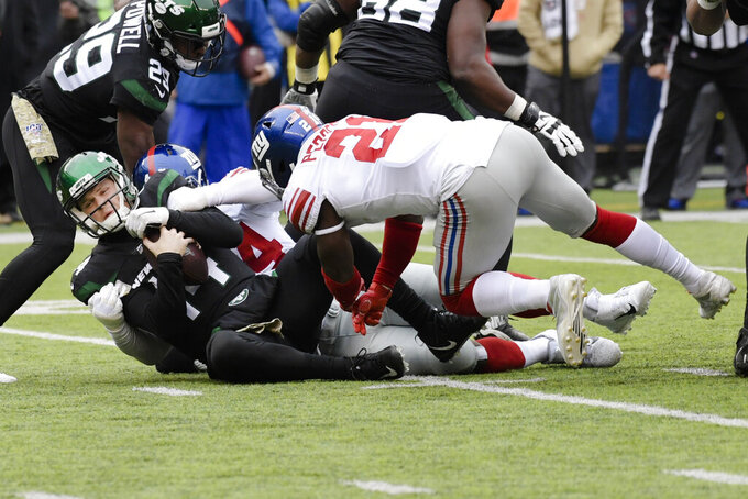 New York Jets quarterback Sam Darnold (14) is sacked by New York Giants' Markus Golden (44) as Jabrill Peppers (21) closes in during the first half of an NFL football game Sunday, Nov. 10, 2019, in East Rutherford, N.J. (AP Photo/Bill Kostroun)