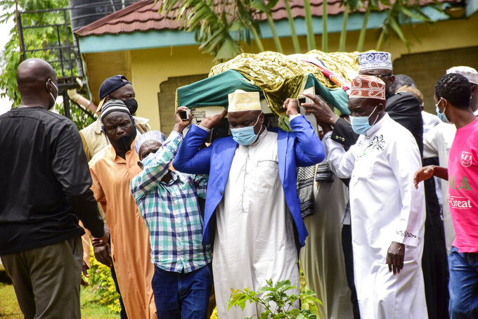 Pallbearers carry the body of Sarah Obama, step-grandmother of President Barack Obama, at her burial in her home village of Kogelo, in western Kenya Tuesday, March 30, 2021. Relatives and officials confirmed on Monday that Sarah Obama, the matriarch of former U.S. President Barack Obama's Kenyan family, has died aged at least 99 years old. (AP Photo/Amos Aura)