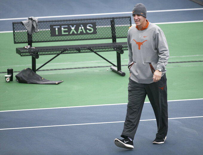 In this January 2018 photo, Texas men's tennis coach Michael Center surveys the courts before the matches with UTSA, in Austin, Texas. Center is among a few people in the state charged in a scheme that involved wealthy parents bribing college coaches and others to gain admissions for their children at top schools, federal prosecutors said Tuesday, March 12, 2019. (Ralph Barrera/Austin American-Statesman via AP)