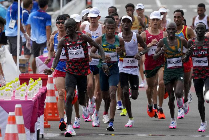 Eliud Kipchoge, of Kenya, grabs a water bottle during the men's marathon at the 2020 Summer Olympics, Sunday, Aug. 8, 2021, in Sapporo, Japan.(AP Photo/Shuji Kajiyama)