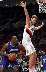 Charlotte Hornets center Bismack Biyombo, left, gets Portland Trail Blazers forward Jake Layman, right, into the air during the first half of an NBA basketball game in Portland, Ore., Friday, Jan. 11, 2019. (AP Photo/Steve Dykes)