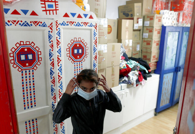 In this photo taken Wednesday, Oct. 28, 2020, a girl puts on her mask in Svratiste, or Roadhouse, Belgrade's first daily drop-in center for street children, in Serbia. For years, a small house tucked away in a Belgrade residential area has been an oasis of warmth and comfort for the Serbian capital's most vulnerable inhabitants  - street children. The Roadhouse drop-in center has served the basic needs of hundreds of children who often have nowhere else to wash, warm up or properly eat.  (AP Photo/Darko Vojinovic)