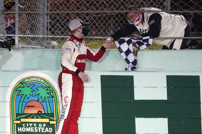 A NASCAR official hands Myatt Snider the checkered flag after Snider won the NASCAR Xfinity Series auto race Saturday, Feb. 27, 2021, at Homestead-Miami Speedway in Homestead, Fla. (AP Photo/Wilfredo Lee)