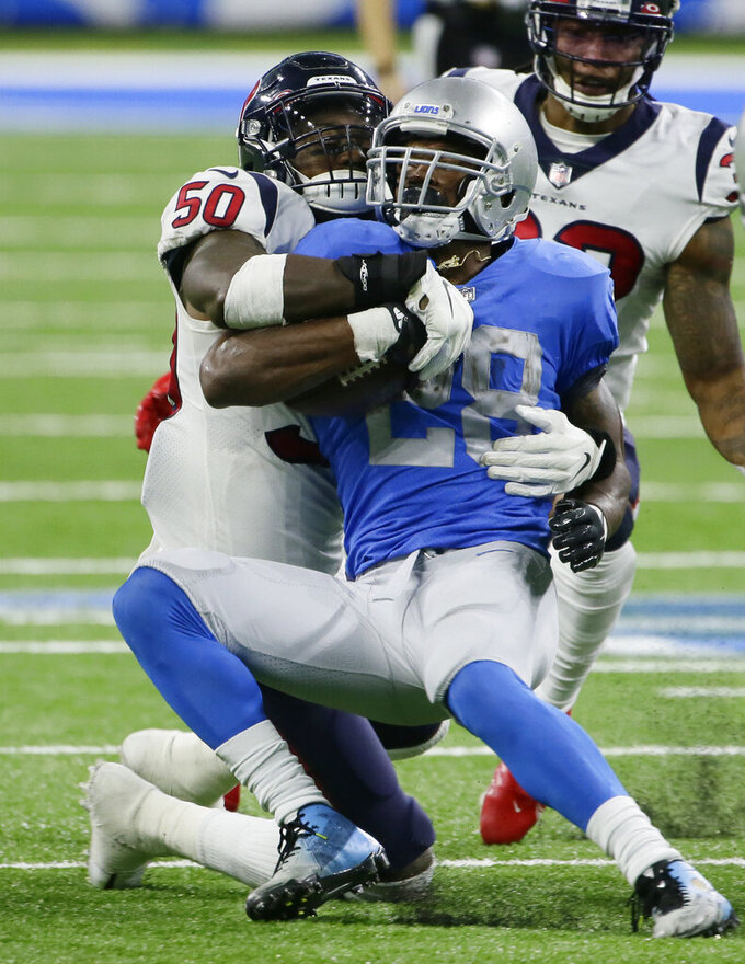 Detroit Lions running back Adrian Peterson (28) is stopped by Houston Texans linebacker Tyrell Adams (50) during the second half of an NFL football game, Thursday, Nov. 26, 2020, in Detroit. (AP Photo/Duane Burleson)