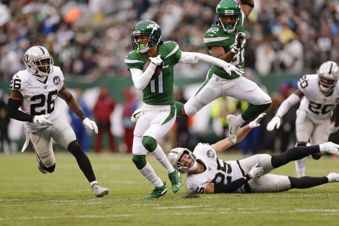 New York Jets wide receiver Robby Anderson (11) runs away from Oakland Raiders free safety Erik Harris (25) and Nevin Lawson (26) during the first half of an NFL football game Sunday, Nov. 24, 2019, in East Rutherford, N.J. (AP Photo/Adam Hunger)
