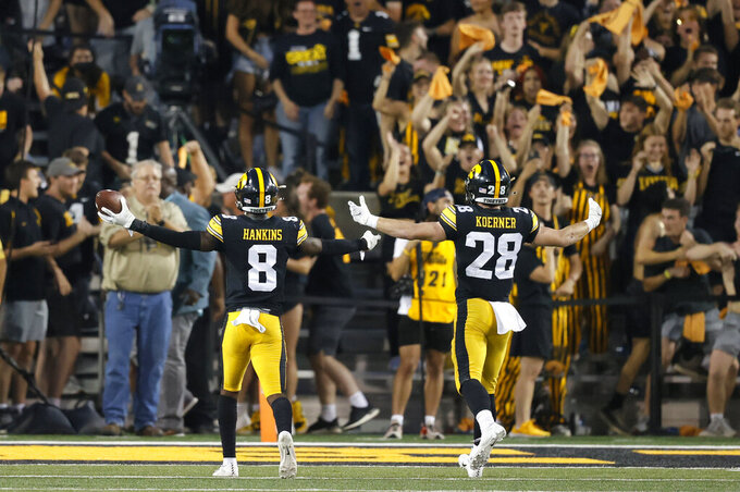 Iowa defensive backs Matt Hankins (8) and Jack Koerner (28) celebrate an interception in the final seconds of an NCAA college football game, Saturday, Oct. 9, 2021, in Iowa City, Iowa. Iowa won 23-20. (AP Photo/Matthew Putney)