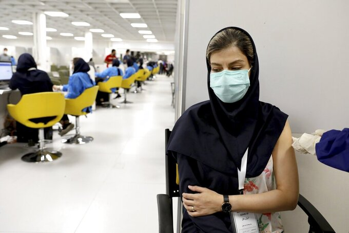 FILE - In this May 17, 2021 file photo, a medical worker receives the Sinopharm coronavirus vaccine at the Iran Mall shopping center in Tehran, Iran. Iran announced on Sunday, July 4, 2021, that it was reimposing coronavirus restrictions on major cities as the spread of the highly contagious delta variant spurs fears of another devastating surge in the nation. (AP Photo/Ebrahim Noroozi, File)