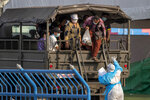 A medical worker in personal protective clothing gestures as migrant workers arrive at a field hospital for COVID-19 patents in Samut Sakhon, South of Bangkok, Thailand, Monday, Jan. 4, 2021. For much of 2020, Thailand had the coronavirus under control. After a strict nationwide lockdown in April and May, the number of new local infections dropped to zero, where they remained for the next six months. However, a new outbreak discovered in mid-December threatens to put Thailand back where it was in the toughest days of early 2020. (AP Photo/Gemunu Amarasinghe)