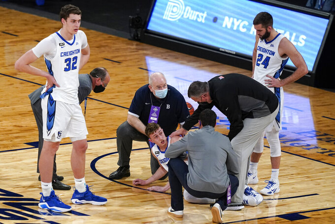 Creighton's Ryan Kalkbrenner (32) and Mitch Ballock (24) watch as coach Greg McDermott checks on Alex O'Connell, who was hurt during the first half of the team's NCAA college basketball game against Butler in the Big East men's tournament Thursday, March 11, 2021, in New York. (AP Photo/Frank Franklin II)