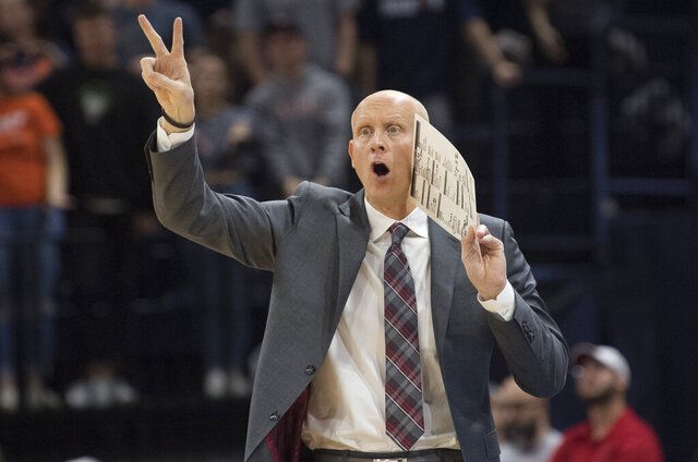 Louisville head basketball coach Chris Mack signal his next play to his team during the second half of an NCAA college basketball game against Virginia in Charlottesville, Va., Saturday, March 7, 2020. (AP Photo/Lee Luther Jr.)