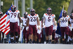 Led by offensive lineman Tyrell Smith (79) and linebacker Rayshard Ashby (23) and defensive lineman Jarrod Hewitt, the Virginia Tech walks onto the field to play Duke in an NCAA college football game, Saturday, Oct. 3, 2020, in Durham, N.C.  (Nell Redmond/Pool Photo via AP)