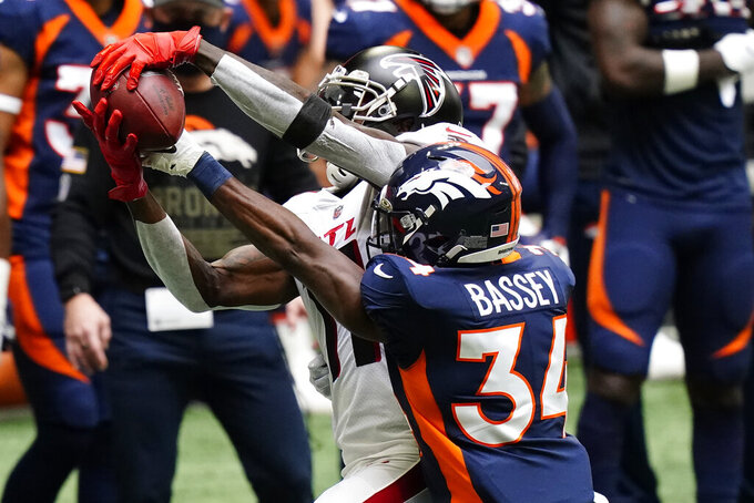 Atlanta Falcons wide receiver Julio Jones (11) makes the catch against Denver Broncos defensive back Essang Bassey (34) during the first half of an NFL football game, Sunday, Nov. 8, 2020, in Atlanta. (AP Photo/Brynn Anderson)