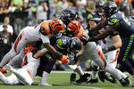 Seattle Seahawks running back Chris Carson (32) is tackled by Cincinnati Bengals' Carlos Dunlap (96) and Geno Atkins (97) during the first half of an NFL football game Sunday, Sept. 8, 2019, in Seattle. (AP Photo/John Froschauer)