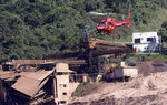 A rescue helicopter transports a body found during a search and recovery effort, days after a dam collapse in Brumadinho, Brazil, Wednesday, Jan. 30, 2019. A torrent of muddy mining waste unleashed by a dam breach that killed at least 84 people in southeastern Brazil is now heading down a small river with high concentrations of iron oxide, threatening to contaminate a much larger river that provides drinking water to communities in five of the country's 26 states. (AP Photo/Andre Penner)