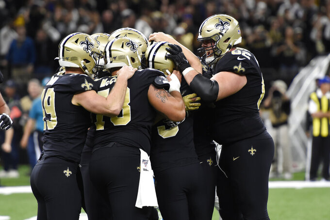 New Orleans Saints teammates crowd around New Orleans Saints kicker Wil Lutz (3), second from right, after Lutz scored the game-winning field goal, during the second half at an NFL football game against the Carolina Panthers, Sunday, Nov. 24, 2019, in New Orleans.The Saints defeated the Panthers 34-31. (AP Photo/Bill Feig)