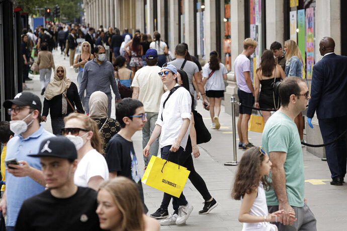 People walk with bags after shopping at the Selfridges department store in London, Monday, June 15, 2020. After three months of being closed under coronavirus restrictions, shops selling fashion, toys and other non-essential goods are being allowed to reopen across England for the first time since the country went into lockdown in March.(AP Photo/Matt Dunham)