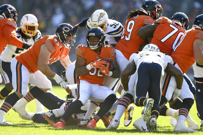 Chicago Bears running back David Montgomery, center, is tackled at the line during the first half of an NFL football game against the Los Angeles Chargers, Sunday, Oct. 27, 2019, in Chicago. (AP Photo/Paul Beaty)