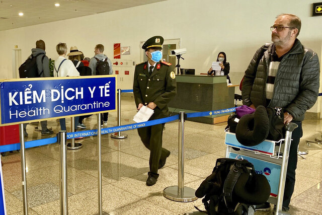 """In this Feb. 20, 2020 photo, passengers stop for health check upon arrival at Noi Bai international airport in Hanoi, Vietnam. Doctors in Vietnam are hoping to perform a lung transplant to save the life of a British pilot, as the Southeast Asian nation seeks to avoid having him become the country's first COVID-19 death. The 43-year-old Vietnam Airlines pilot, known according to privacy rules as """"Patient 91,"""" tested positive for the coronavirus in March in Ho Chi Minh City and is being treated there at the Hospital for Tropical Diseases.(AP Photo/Hau Dinh)"""